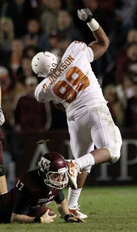Texas defensive lineman Desmond Jackson (99) celebrates after sacking Texas A&M quarterback Ryan Tannehill (17) during the fourth quarter of an NCAA college football game at Kyle Field Thursday, Nov. 24, 2011, in College Station. Texas beat Texas A&M 27-25. Photo: Brett Coomer, Houston Chronicle / © 2011 Houston Chronicle