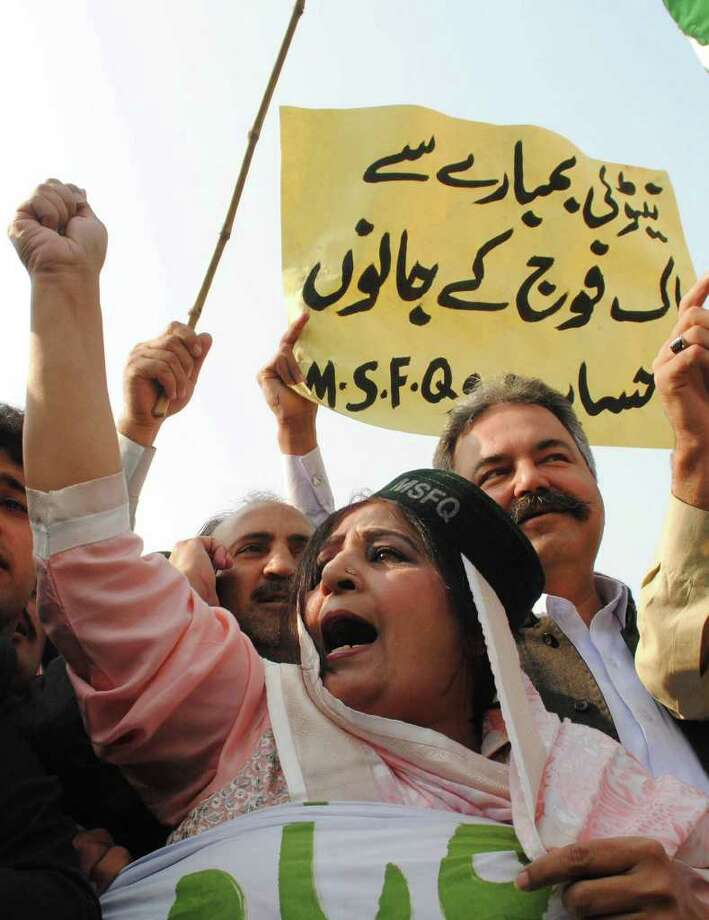 "A Pakistani woman joins other to condemn NATO strikes on Pakistani posts, in Peshawar, Pakistan on Monday, Nov. 28, 2011. The NATO airstrikes that killed 24 Pakistani soldiers went on for almost two hours and continued even after Pakistani commanders had pleaded with coalition forces to stop, the army claimed Monday in charges that could further inflame anger in Pakistan. A placard reads ""NATO is responsible for the loss of Pakistani soldiers."" (AP Photo/Mohammad Sajjad) Photo: Mohammad Sajjad / AP"