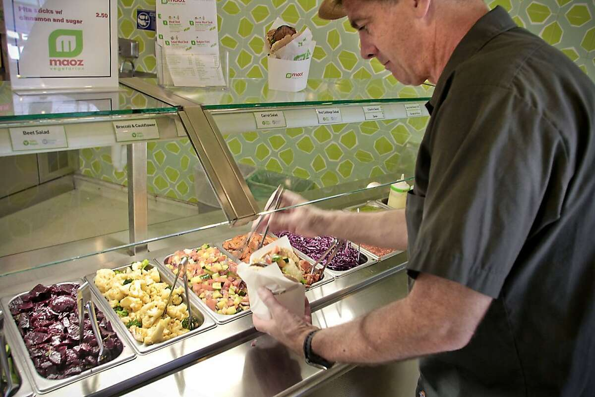 A diner fills his Maoz sandwich with veggies at Maoz Vegetarian restaurant in Berkeley, Calif., on June 15th, 2011.