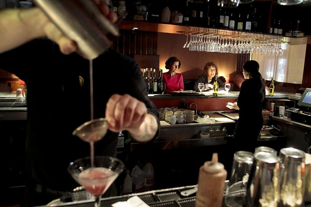 A waitress takes an order for dinner as a cocktail is strained at Millennium restaurant In San Francisco, Calif., on June 17th, 2011.