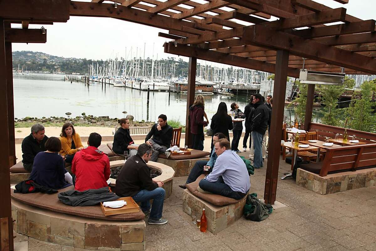 Customers mingle over wine, beer and fresh food around the fire pit of Bar Bocce.