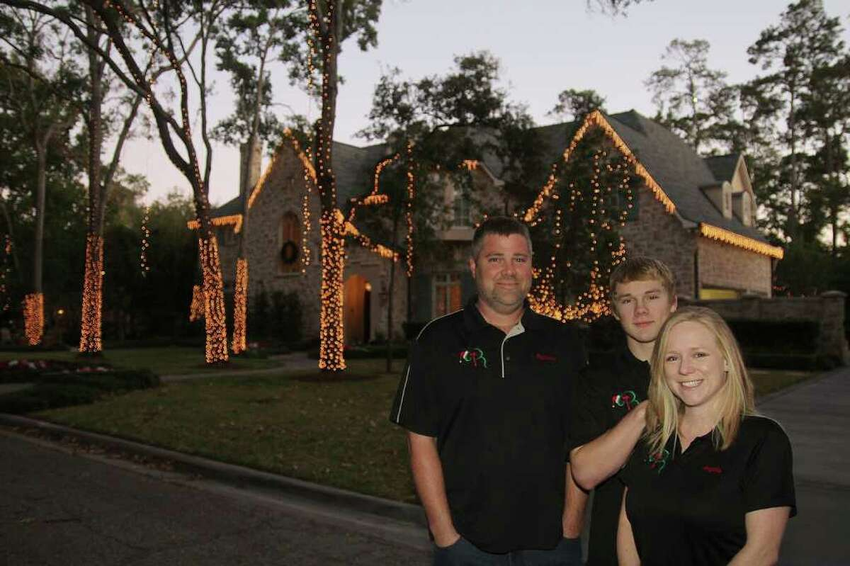 PIN LIM: FOR THE CHRONICLE INSTANT MAGIC: Raymond and Angel Brown, with their son, Evan, are owners of Deer Park-based RT Holiday Services. The company created a lighting display for the Jorgensen family's home, among others, in the Greater Houston area.