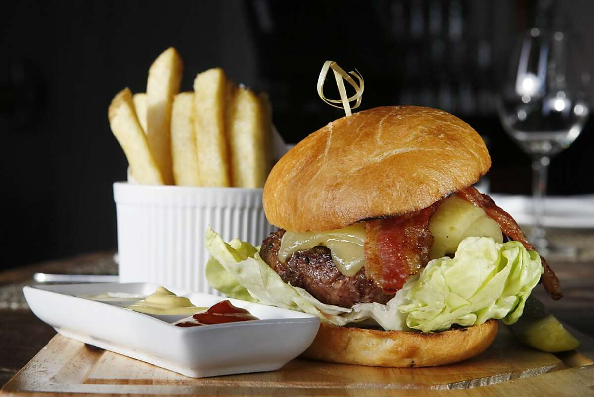 The half pound hamburger comes with steak fries, butter lettuce, bacon and cheese at Hudson in Oakland Calif, on Tuesday, April 12, 2011.