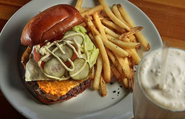 The Cheeseburgerr with a Salted Coffee Caramel Milkshake at Greenburger's Restaurant in San Francisco, Calif. is seen on Sunday, April 10th,  2011.  Ran on: 04-21-2011 At Greenburger's, homemade mayonnaise highlights a Five Dot Ranch burger, served on a toasted brioche bun. The restaurant features vintage Americana, including the case that houses condiments and the framed family photographs on the walls. Photo: John Storey, Special To The Chronicle