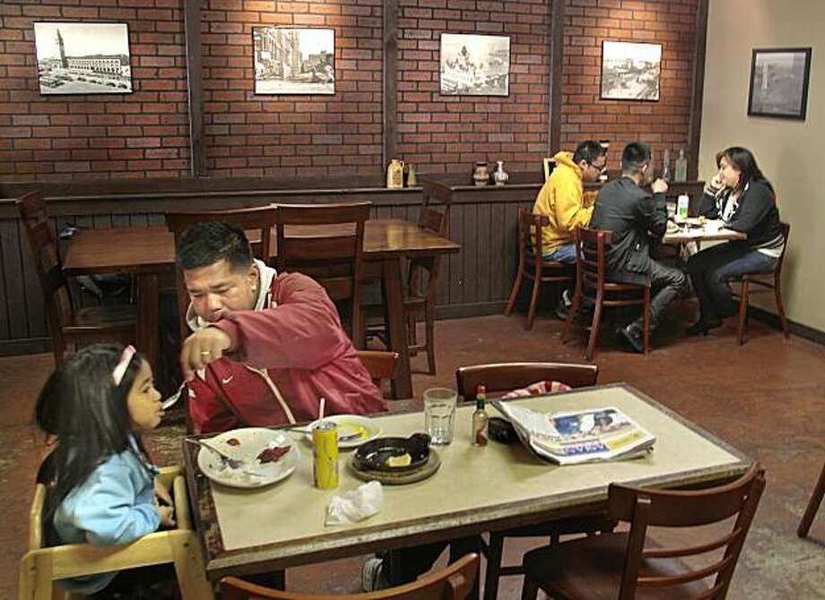 Diners enjoy lunch at Tselogs restaurant in Daly City,  Calif., on Friday,  February 25th,  2011.  Ran on: 03-03-2011 Tselogs in Daly City is a Filipino cafe that serves up tapas plates, or silogs, of such fare as chicken sisig and lumpiang Shanghai, right, with fried rice and a fried egg. Below: Oliver Santos fires up the kitchen. Photo: John Storey, Special To The Chronicle
