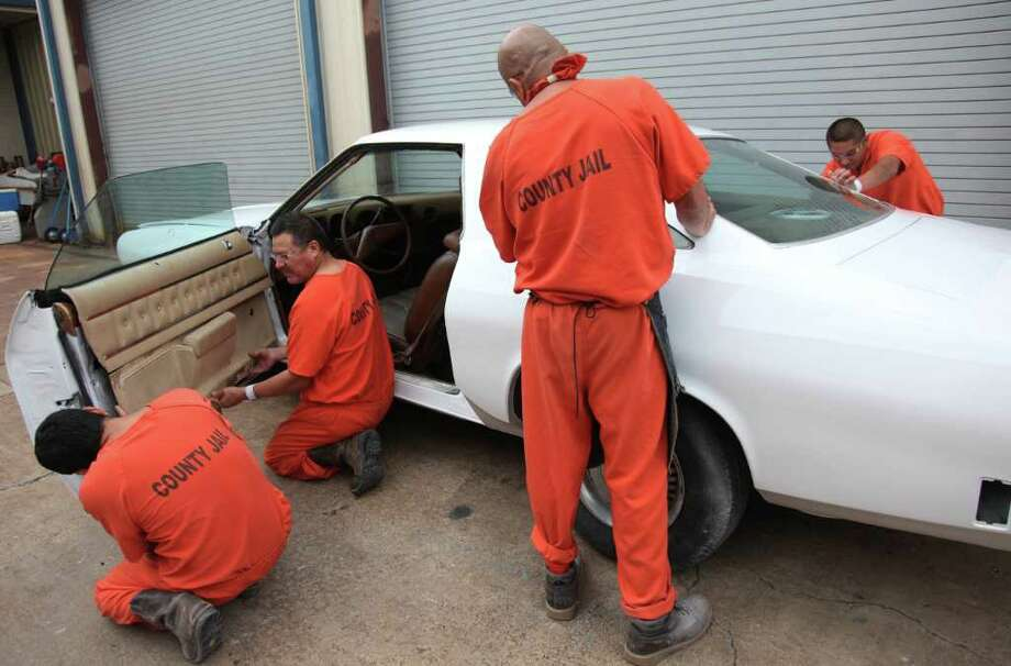 MAYRA BELTRÁN : CHRONICLE ASSEMBLY REQUIRED: Marcos Perea, 40, left, Martin Sanchez, 49, Miguel Rodriguez, 45, and Jose Miguel Bences, 19, reassemble a car after painting it during an auto repair class that helps inmates learn a trade before release. Photo: Mayra Beltran / © 2011 Houston Chronicle
