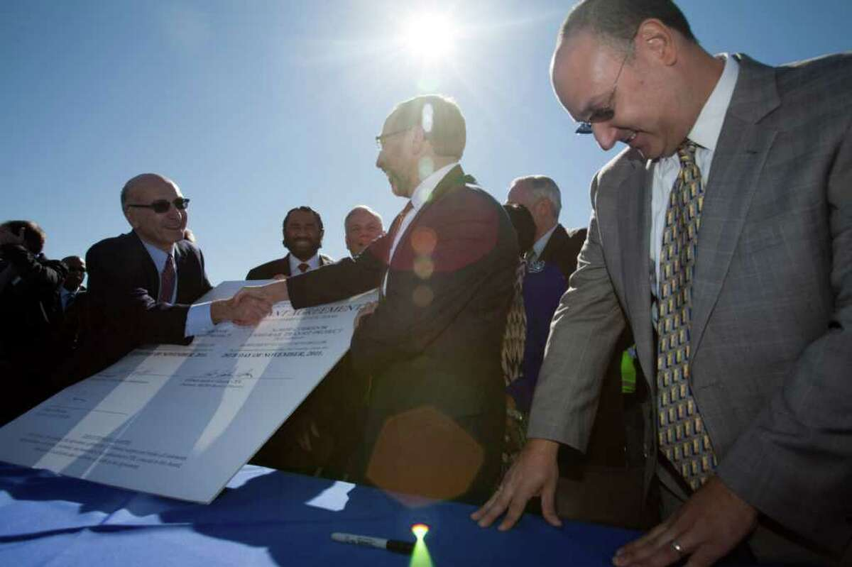 Metro CEO George Greanias, left, Federal Transit Administrator Peter Rogoff, and Metro chairman Gilbert Garcia symbolically signed a light rail grant for Metro totaling $900 million in 2011 in Houston.