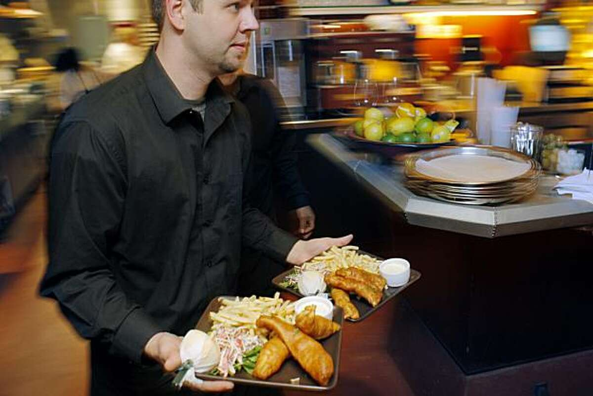 David Samuelson carry two plates of fish and chips out of the kitchen at Zut! on Friday, December 17, 2010, Berkeley, Calif.