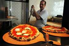 Zero Zero Chef Chris Whaley pulls out a Margherita Extra pizza made with buffalo mozzarella cheese from the wood fired brick oven. Photo was taken Saturday, Sept. 25, 2010.