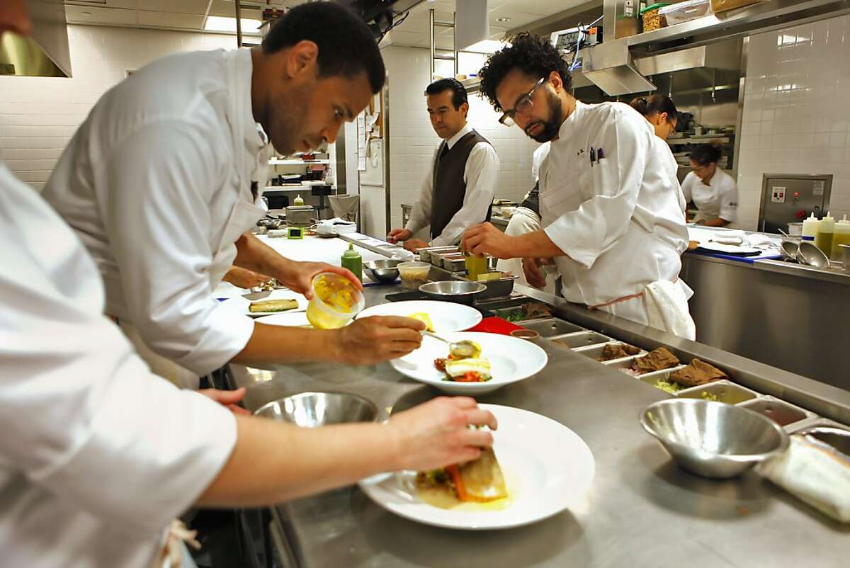 Customers enjoy chef, Ravi Kapur, right, watches as he prepares dinner,Thursday August 26, 2010, at the Prospect restaurant in San Francisco, Calif.