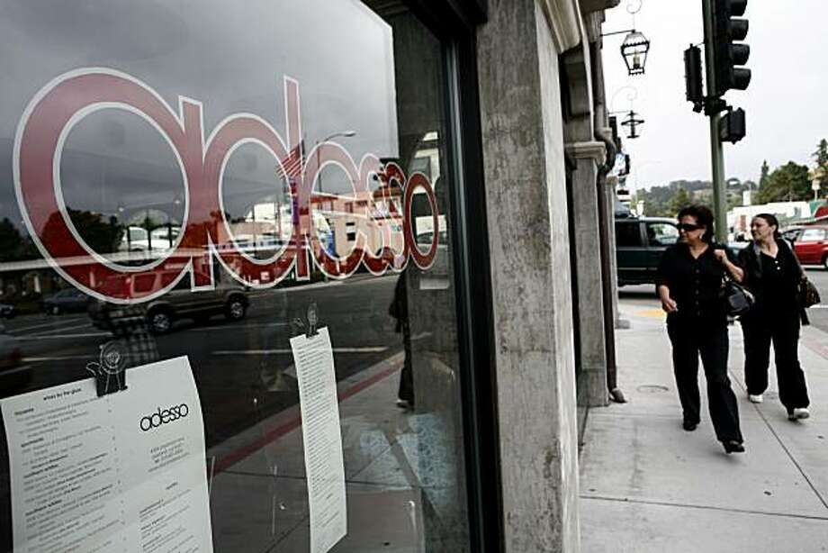 Two women peer into Adesso's windows as they walk past the restaurant during happy hour on Tuesday, July 6, 2010 in Oakland, Calif. Photo: John Sebastian Russo, The Chronicle