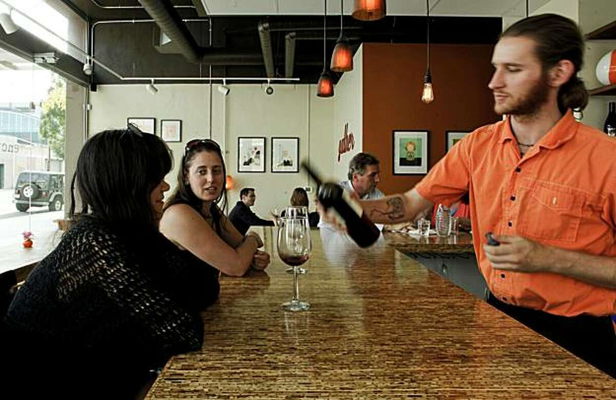 Sarah Brady, (left) and Aimee Voyde of Oakland, are served wine by August Beck at Encuentro restaurant near Jack London Square in Oakland, Ca. on Tuesday June 22, 2010.
