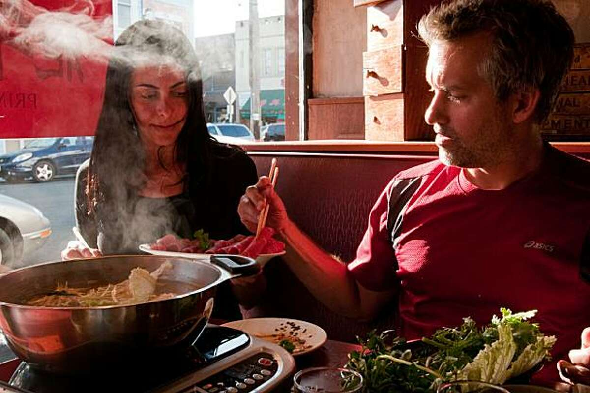 Luciana Casado, 39, of San Francisco, Calif., holds a plate of thin-cut lamb shoulder for Eric Troyer, 36, also of San Francisco, at Prime Rib Shabu in the Richmond district of San Francisco, Calif., on June 19, 2010.