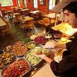 A server prepares a falafel sandwich at Amba in Oakland.
