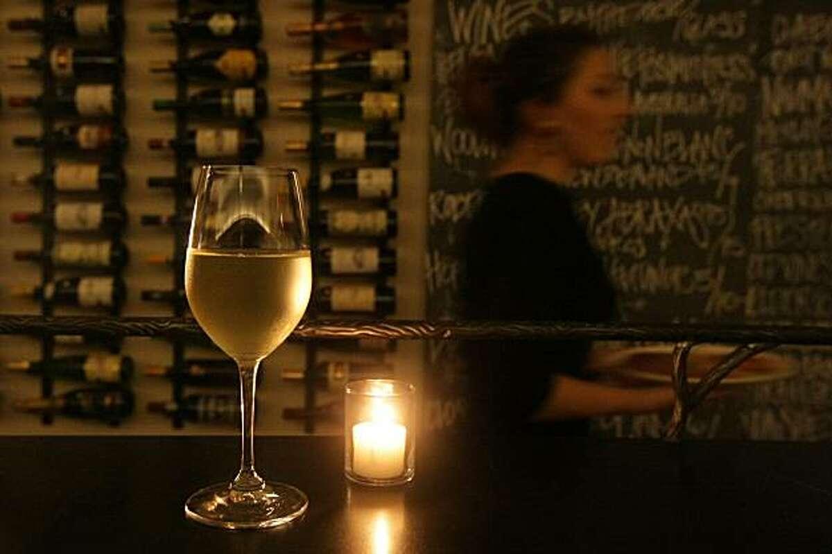 A glass of HŸpler Gruner Veltliner, an Austrian white, sits on a bar at Red + White Wine Bar in the Glen Park neighborhood of San Francisco, CA Friday night, February 26, 2010.