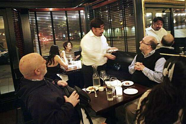 A server delivers a course from the prix fixe menu to Kenneth Caldwell (right) and Alvin Baum (left) at Baker and Banker on Tuesday February 16, 2010 in San Francisco, Calif. Photo: Lea Suzuki, The Chronicle