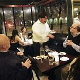 A server delivers a course from the prix fixe menu to Kenneth Caldwell (right) and Alvin Baum (left) at Baker and Banker on Tuesday February 16, 2010 in San Francisco, Calif.