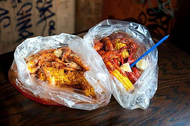 Shrimp (left) and crawfish are among the most popular dishes at The Boiling Crab and are served by the pound, carried to the table in tin buckets then presented in plastic bags sitting in a pool of the signature sauce that you choose. Photo: Chad Ziemendorf, Special To The Chronicle