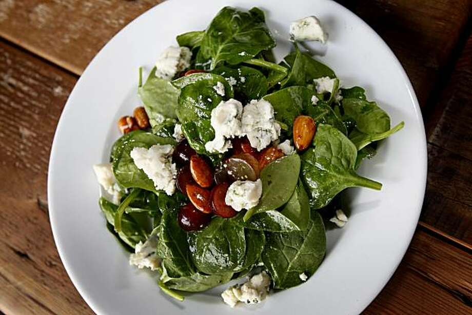 A baby spinach salad with candied almonds, blue cheese and grapes. The Chop Bar in Oakland features a large airy dining area with a rounded bar near the kitchen. Photo: Brant Ward, The Chronicle