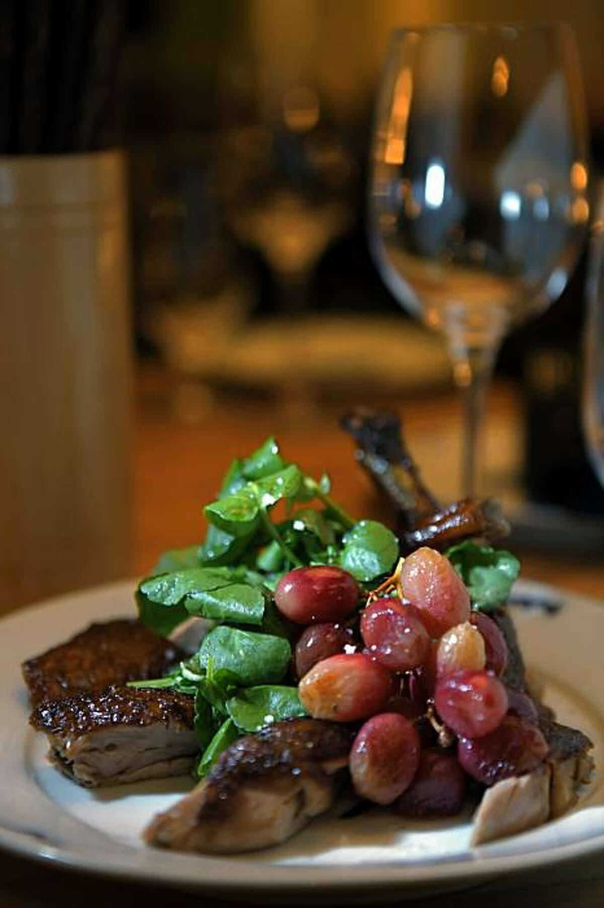 The half rotisserie fragrant duck with upland cress, and roasted grapes, served at OTD. OTD is Charles Phans new restaurant. Photos of the interior and a 360 for the Gate.