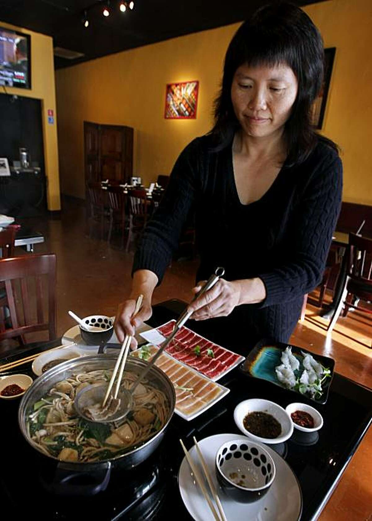 Necole Chu helps a diner cook chicken, beef and mushrooms in a hot pot of broth at Ray's Hot Pot restaurant in San Rafael, Calif., on Wednesday, Dec. 9, 2009.