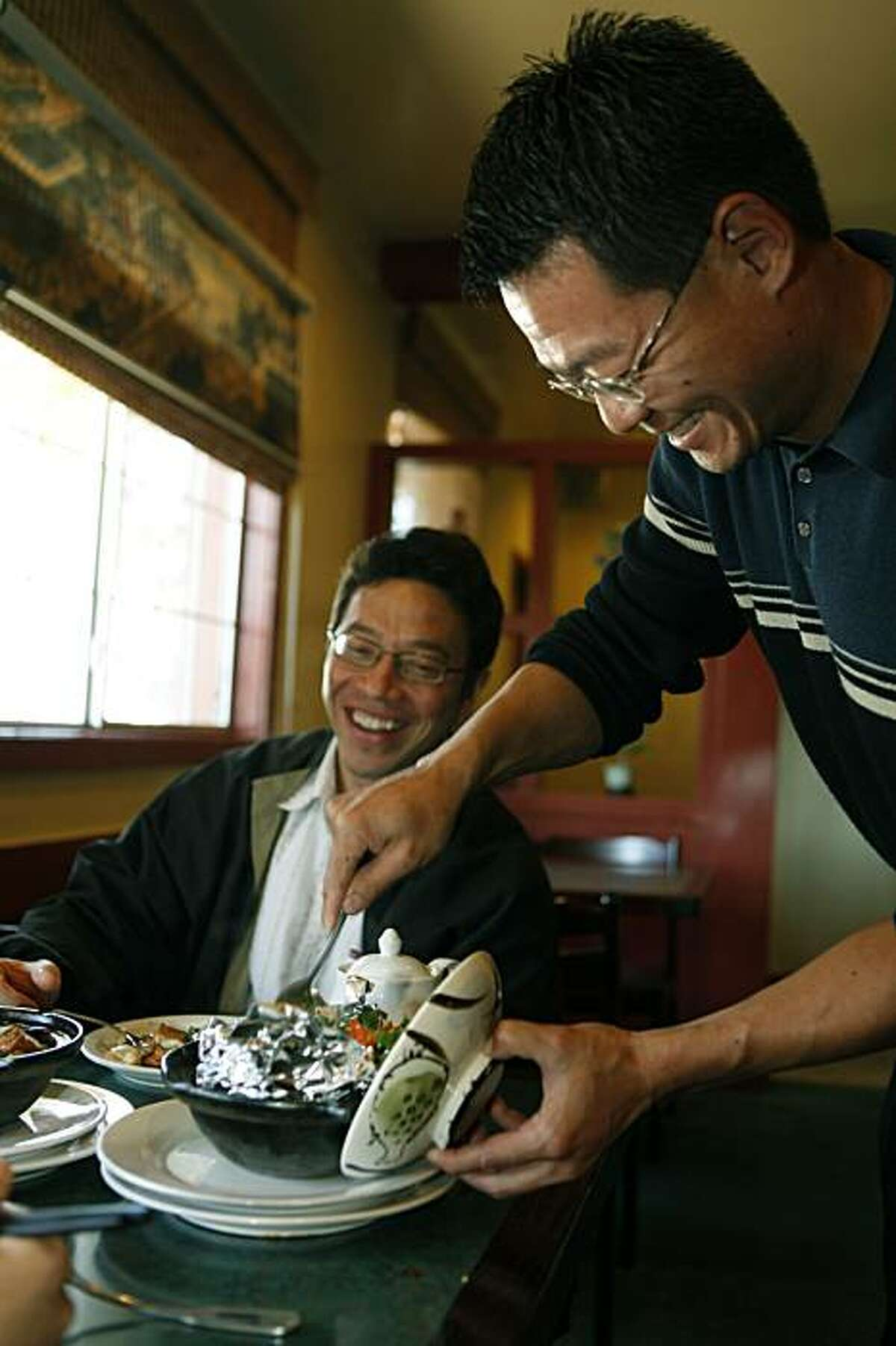 Allen Shi right, from Sichuan Fortune House in Concord serves Changsha Chicken in a Clay Pot to Mark Kurashige from Concord.Tuesday November 24, 2009.