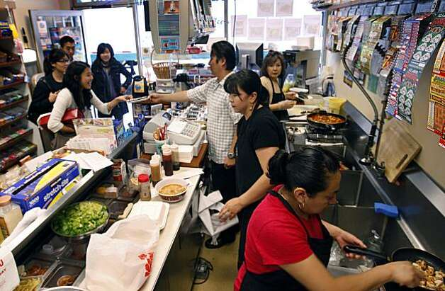 Customers crowd into John's Snack and Deli (top left) where John Park and his mom and staff prepare tasty Korean food in San Francisco, Calif., on Tuesday, July 7, 2009. Ran on: 07-16-2009 Sang Sook Park, near right, always rolls fresh kimbap, far right, which is Korean-style maki made with toasted sesame oil rice, carrots, pickled daikon, cucumber and a choice of beef, Spam or vegetables. Park works with her son John, creating homemade Korean food at John's Snack and Deli, above, in the Financial District. Photo: Paul Chinn, The Chronicle