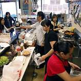 Customers crowd into John's Snack and Deli (top left) where John Park and his mom and staff prepare tasty Korean food in San Francisco, Calif., on Tuesday, July 7, 2009. Ran on: 07-16-2009 Sang Sook Park, near right, always rolls fresh kimbap, far right, which is Korean-style maki made with toasted sesame oil rice, carrots, pickled daikon, cucumber and a choice of beef, Spam or vegetables. Park works with her son John, creating homemade Korean food at John's Snack and Deli, above, in the Financial District.