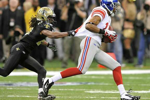 New Orleans Saints cornerback Patrick Robinson (21) grabs the jersey of New York Giants wide receiver Ramses Barden (13) during the first quarter of an NFL football game in New Orleans, Monday, Nov. 28, 2011. (AP Photo/Bill Feig)
