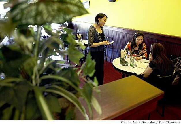 Yshel Lok, left, waits on sisters Tran and Tram Nguyen of El Cerrito, at Kopitiam, a Singaporean cafe in Lafayette, Calif., on Wednesday, April 22, 2009. Photo: Carlos Avila Gonzalez, The Chronicle