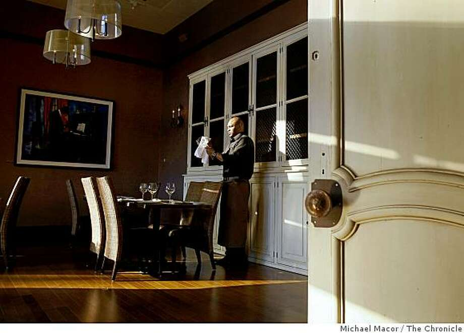 """A smaller dining off the main, incorporates French 18th century farmhouse doors at it's entrance, at """"Pican"""" a taste of the south, restaurant, on Broadway in downtown Oakland, Calif., on Tuesday March 24, 2009. Server Terrance Brunson prepares for the evenings' patrons. Photo: Michael Macor, The Chronicle"""