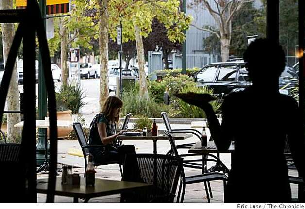 Waitress Bethanie Hines takes an order out to the sidewalk dining area where Amanda Farris, background,  is having breakfast at Cafe M in Berkeley photographed on Thursday, October 2, 2008. Photo: Eric Luse, The Chronicle