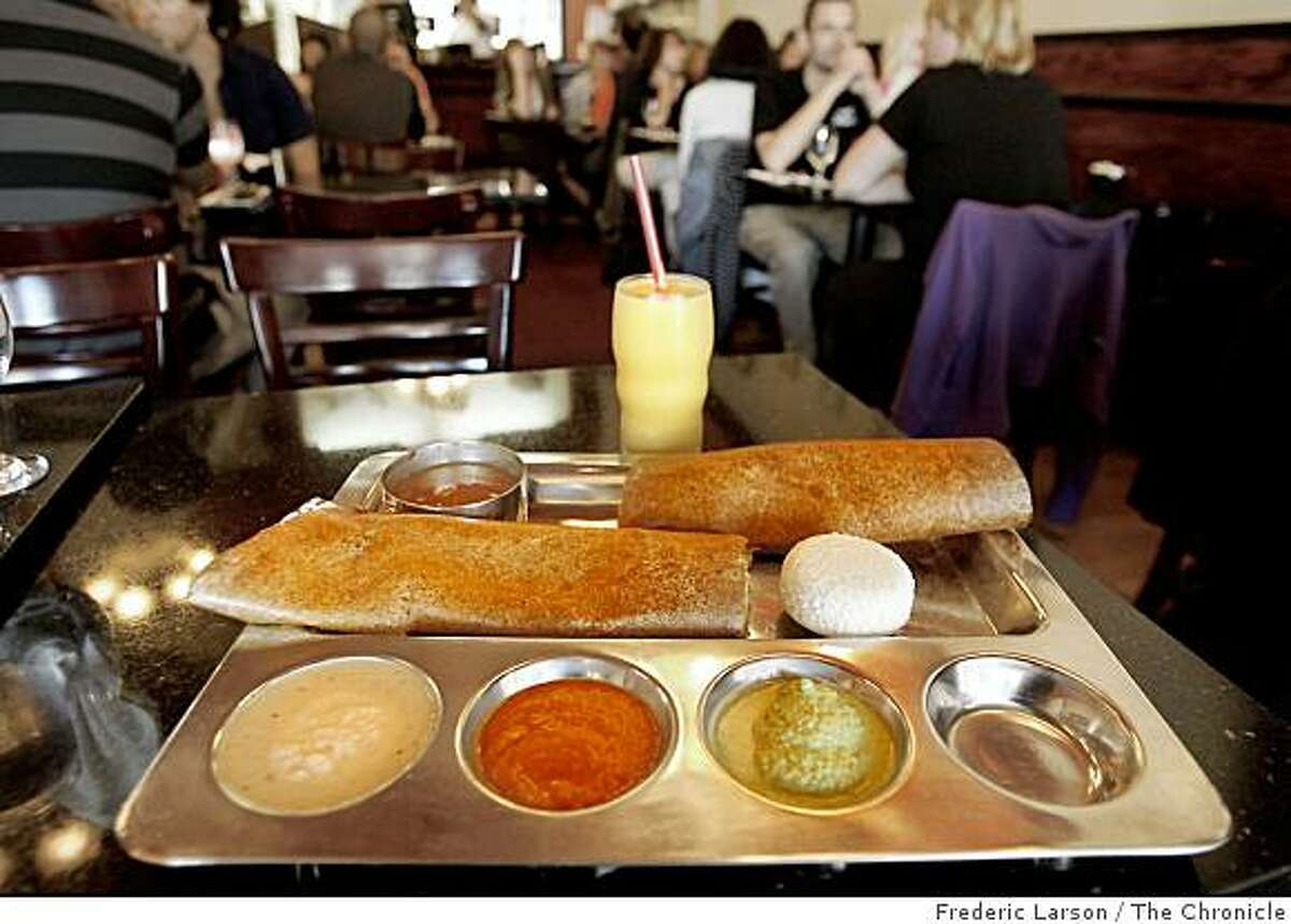 The of the most popular dishes at the Udupi Palace restaurant on Valencia Street in San Francisco, California on August 21, 2008 is the Spinach Masala Dosa with a Mango Lassi Sweet Mango Yogart drink.