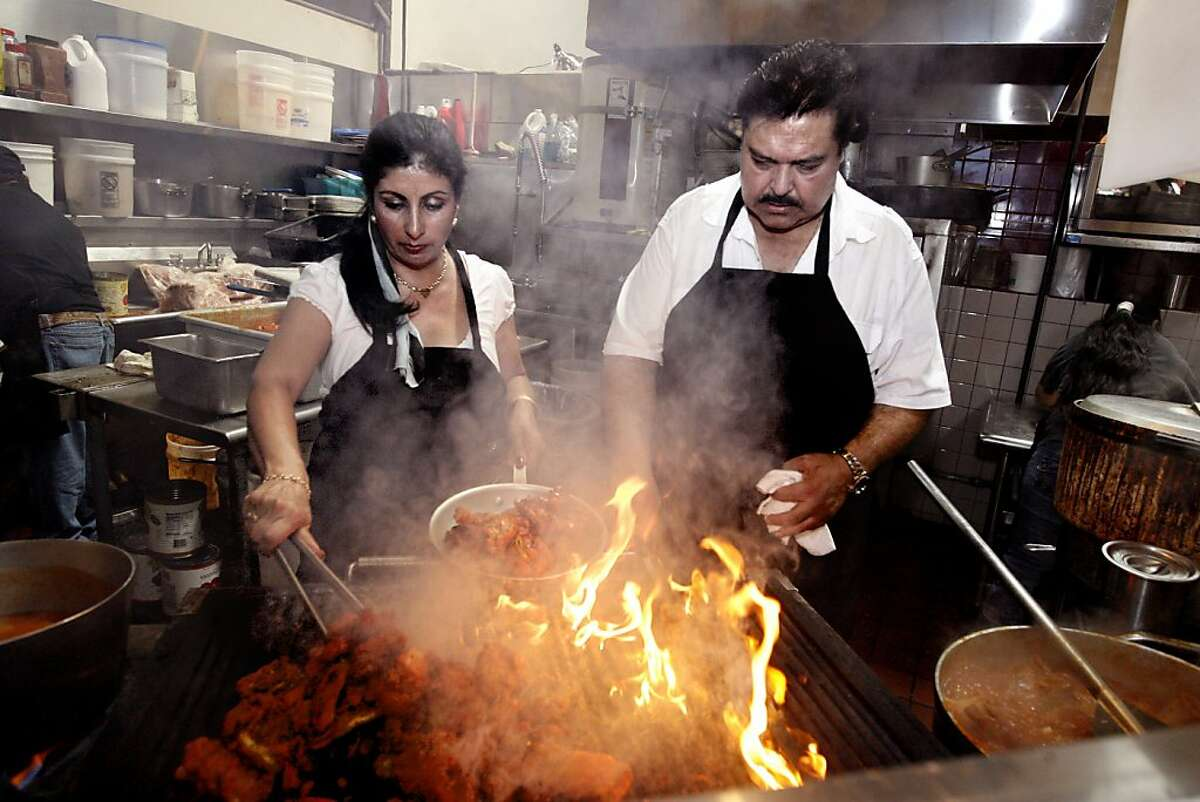 Owner and chef Ahmed Esmatyar, right, and his wife Malika Esmatyar, left, work the grill at Pamir Afghan Cuisine, one of the many ethnic restaurants in the Emery Bay Public Market, in Emeryville, Calif. on Monday, Aug. 11, 2008. Ran on: 08-21-2008 Owner and chef Ahmad Esmatyar, and his wife, Malika, work the grill at Pamir Afghan Cuisine in EmeryBay Public Market. The restaurant produces standout vegetarian and meat dishes, such as the kebab Soltani, below, which combines lamb or beef kebab with ground meat kebab and barbecue chicken for $9.99.