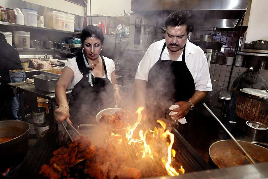 Owner and chef Ahmed Esmatyar, right, and his wife Malika Esmatyar, left, work the grill at Pamir Afghan Cuisine, one of the many ethnic restaurants in the Emery Bay Public Market, in Emeryville, Calif. on Monday,  Aug. 11, 2008.  Ran on: 08-21-2008 Owner and chef Ahmad Esmatyar, and his wife, Malika, work the grill at Pamir Afghan Cuisine in EmeryBay Public Market. The restaurant produces standout vegetarian and meat dishes, such as the kebab Soltani, below, which combines lamb or beef kebab with ground meat kebab and barbecue chicken for $9.99. Photo: Katy Raddatz, The Chronicle