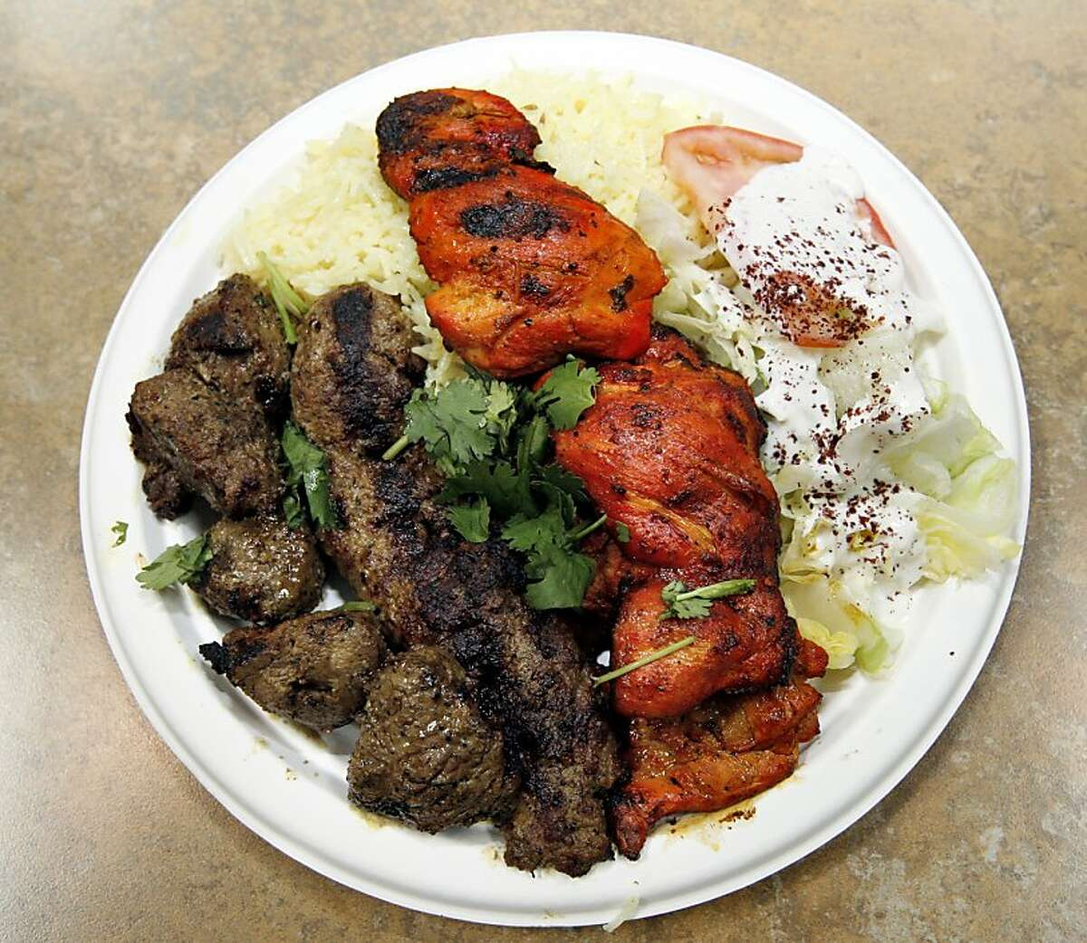 The Combo Kabab at Pamir Afghan Cuisine, one of the many ethnic restaurants in the Emery Bay Public Market, in Emeryville, Calif. on Monday, Aug. 11, 2008. Ran on: 08-21-2008 Owner and chef Ahmad Esmatyar, and his wife, Malika, work the grill at Pamir Afghan Cuisine in EmeryBay Public Market. The restaurant produces standout vegetarian and meat dishes, such as the kebab Soltani, below, which combines lamb or beef kebab with ground meat kebab and barbecue chicken for $9.99.
