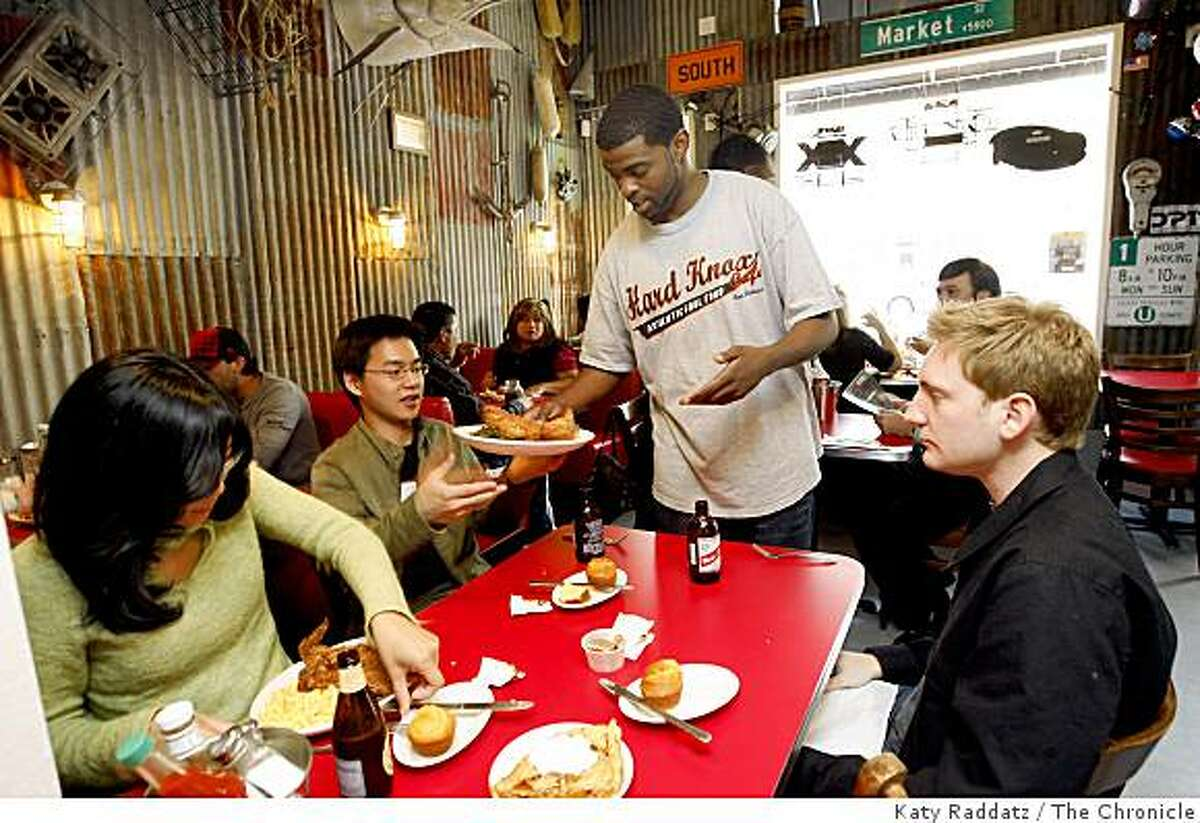 Waiter Rance Hodge serves dinners at the Hard Knox Cafe on Clement St., in San Francisco.