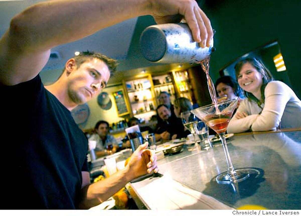 � CESAR_7570.JPG Ce'sar bartender Alex Conde pours a martini as Christina Dalton from Oakland looks on. Ce'sar, located at 4039 Piedmont Ave in Oakland is a local favorite that serves tapas style dishes that include Bistec a la Mirabeau, A grilled hanger steak with olive butter & grilled chicories, Shrimp dish called Gambas a la Gallego, or grilled grape leaf-wrapped salmon on a bed of pine nuts & rice, patatas bravas. March 30, 2007, in Ce'sar, (cq, menu) Photo By Lance Iversen / The Chronicle Photo taken on 3/30/07, in OAKLAND, CA. MANDATORY CREDIT PHOTOG AND SAN FRANCISCO CHRONICLE/NO SALES MAGS OUT