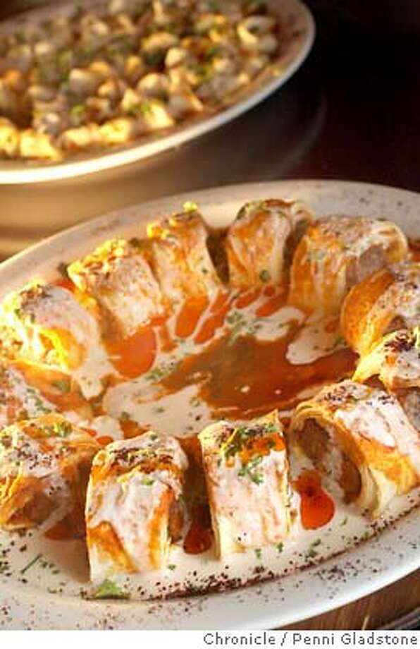 dine05_troya  Troya is a Turkish restaurant  In the back is, Manti - Homemade mini ravioli, stuffed with ground beef, topped with homemade garlic yogurt and melted paprika butter.  In front is, Beyti - Ground lamb in lavash bread roulade, topped with tomato sauce, homemade garlic yogurt sauce and melted paprika butter.  Event on 1/2/07 in San Francisco.  Penni Gladstone / The Chronicle MANDATORY CREDIT FOR PHOTOG AND SF CHRONICLE/ -MAGS OUT Photo: Penni Gladstone