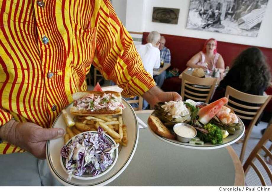 Jamis MacNiven, the restaurant owner's father, displays the lobster roll (left) the stuffed artichoke before serving them to customers at the Woodhouse Fish Company restaurant in San Francisco, Calif. on Tuesday, August 8, 2006.  PAUL CHINN/The Chronicle  **Jamis MacNiven MANDATORY CREDIT FOR PHOTOGRAPHER AND S.F. CHRONICLE/ - MAGS OUT Photo: PAUL CHINN