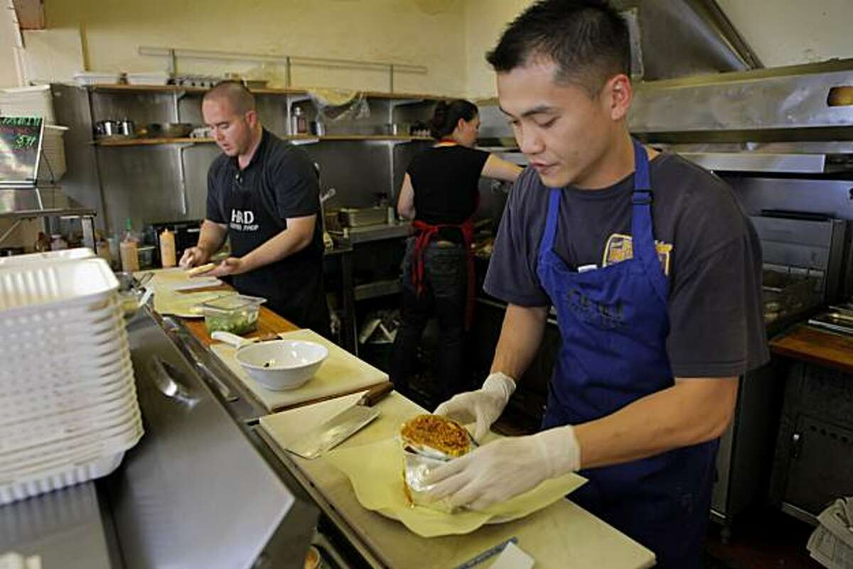 """New owners Marc Rubio, back left, Joanna """"JoJo"""" Banks, and David Yeung, of the HRD Coffee Shop work behind the counter, Wednesday June 16, 2010, in San Francisco, Calif. The Coffee Shop has been on Third Street for more than 40 years, but is now under new management."""