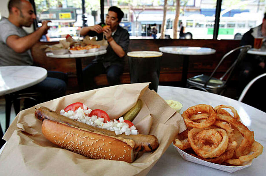 Ryan Farr's organic 4505 Dog--diced onion, sliced tomato, housemustard-- onion rings and Barney Flats Oatmeal Stout at Showdogs, a gourmet hotdog emporium from the owners of Foreign Cinema on the corner of 6th on Market streets in San Francisco Calif., on Friday, August 14, 2009. Photo: Liz Hafalia, The Chronicle / SFC