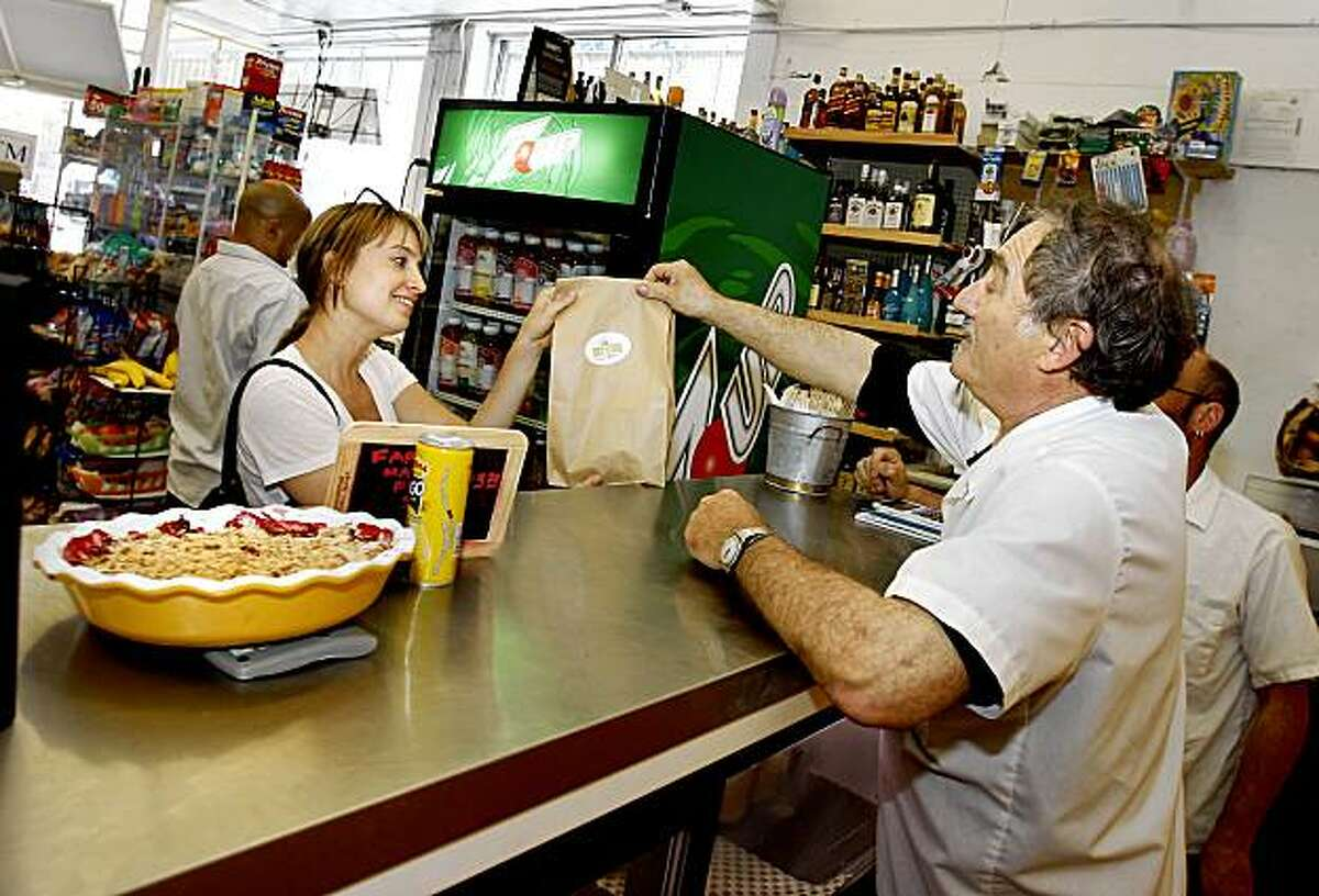 Pal's Take Away owner Jeff Mason (right) serves another customer at the popular restaurant. Pal's Take Away is located inside Tony's Market at the end of 24th Street near Potrero.