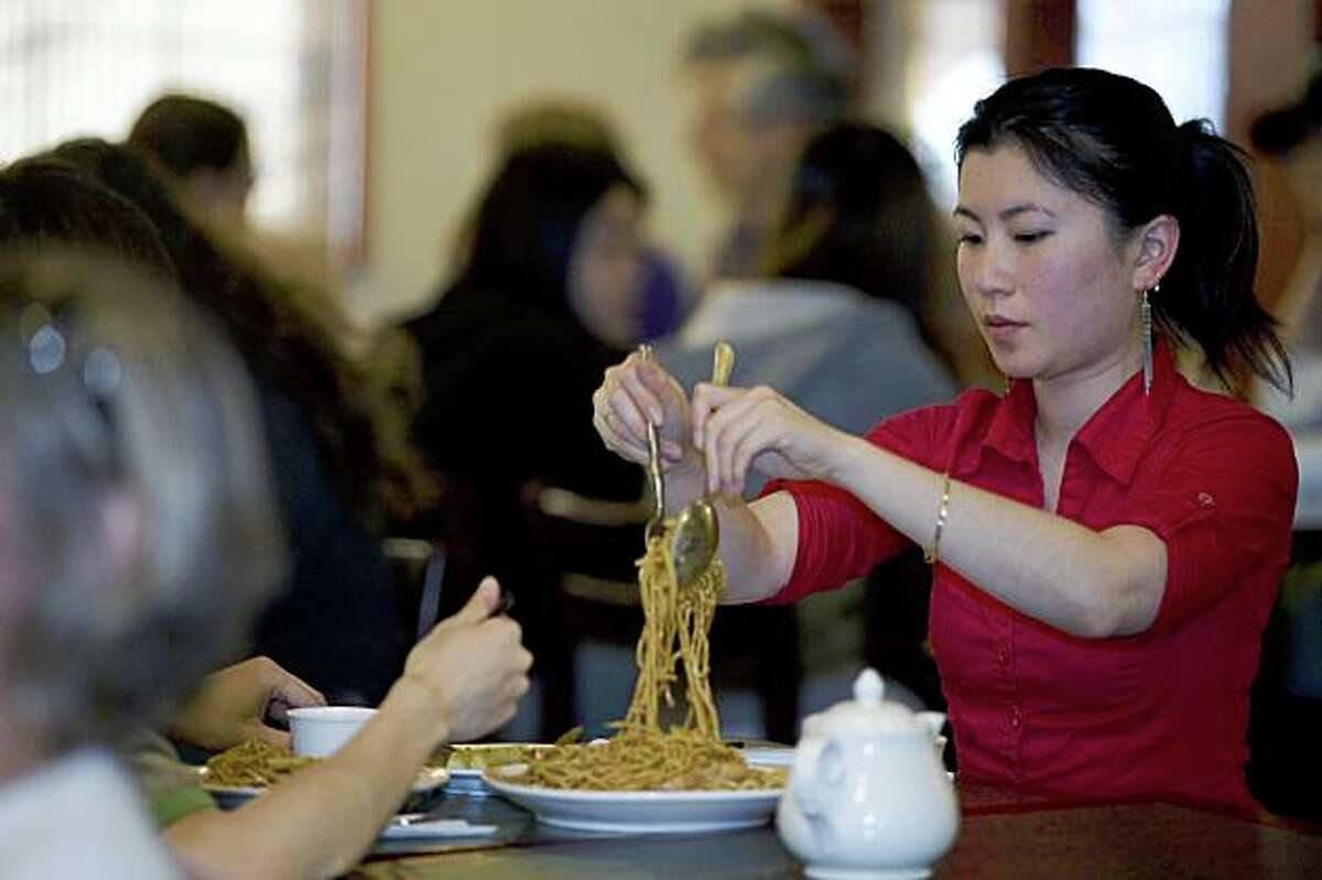 Judy Liang from Napa , serves her friend Kelvin Wong, from Pinole as the pair dine on the Szchehan cuisine at Sichuan Fortune House in Pleasant Hill, Calif. on Thursday, June 4, 2009. Photo by Kat Wade / Special to the Chronicle