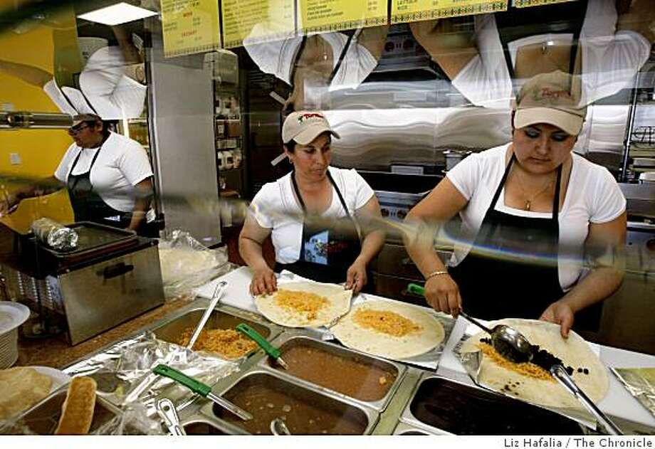 Gabie Sanchez (far left) checking out orders as Nellie Velasco (middle) and manager Mayra Garcia (right) make burritos at Tortillas Mexican Grill in Millbrae, Calif., on Thursday, May 28, 2009. Photo: Liz Hafalia, The Chronicle