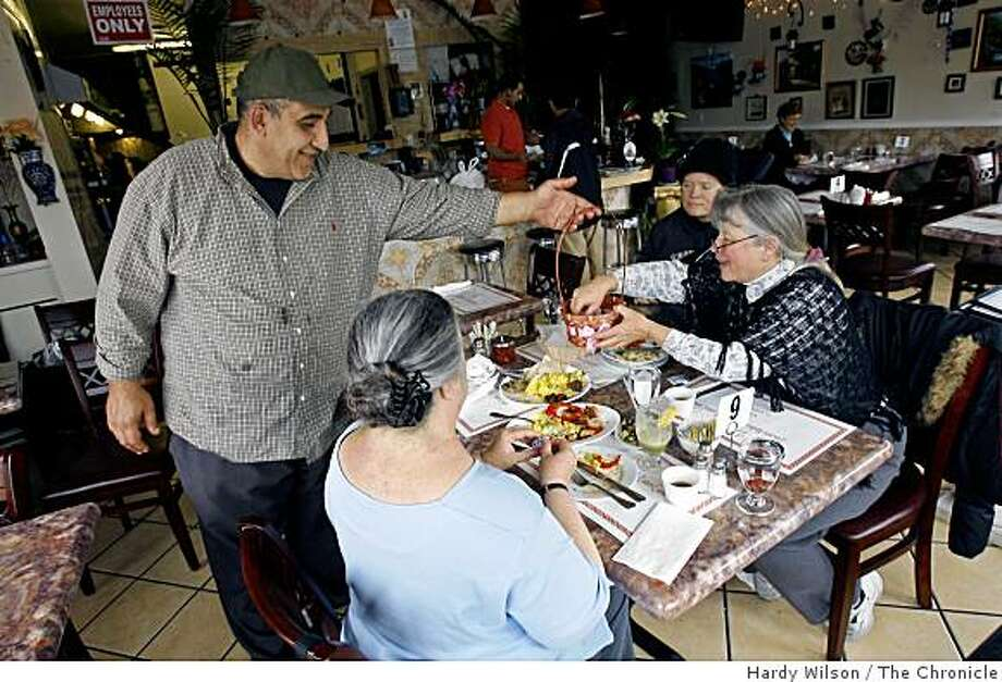 Kamem Muhammed, left, serves Shelley Robinson, top center, her mother Lin Robinson, right, and Julie Sager during lunch service at Zaki Kabob House in Albany, Calif., on Tuesday, April 7, 2009. Photo: Hardy Wilson, The Chronicle