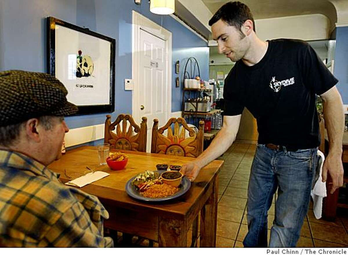 Chris Patella (right) brings a lunch order to a diner at Little Chihuahua taqueria in San Francisco, Calif., on Tuesday, April 14, 2009.