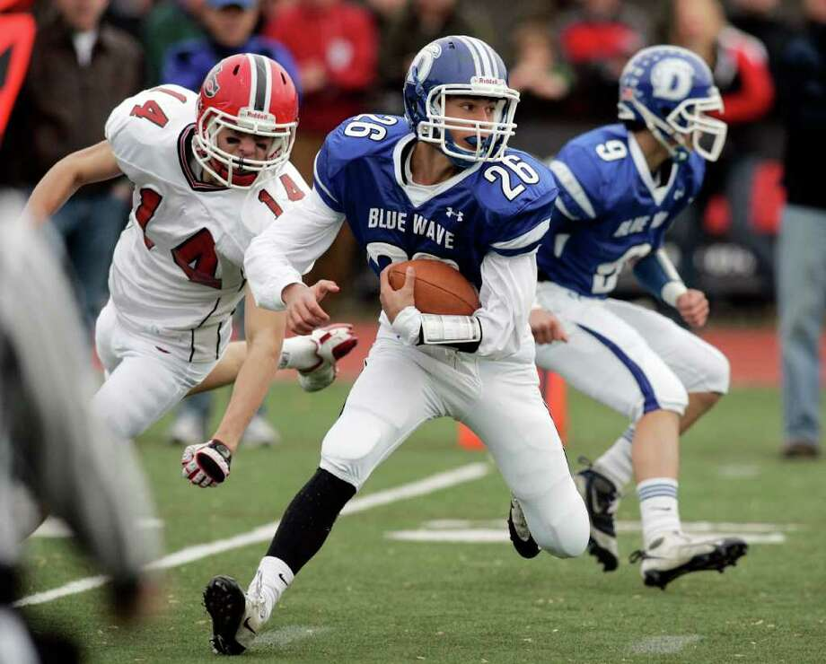 Darien running back Peter Gesualdi looks from running room during first quarter action against New Canaan. Ram defender Dylan Leeming trails the play. Photo: J. Gregory Raymond, ST / © J. Gregory Raymond for Stamford Advocate Freelance