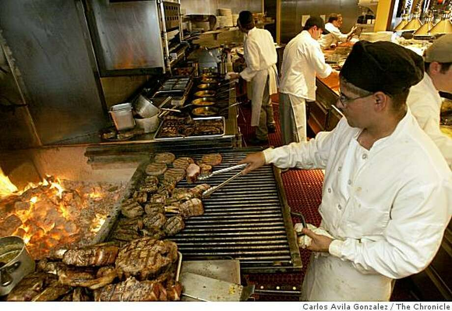Jorge Ruiz cooks some grass-fed beef at ACME Chophouse at Pacific Bell Park in San Francisco, Ca., on Tuesday, June 18, 2002. The restaurant is one of the few in the city to serve the fine meats. Photo: Carlos Avila Gonzalez, The Chronicle