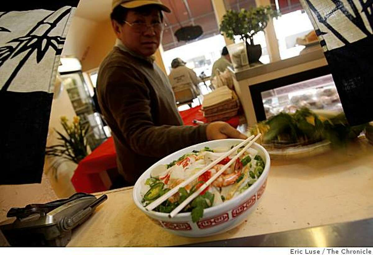David Huynh, owner Linda Lam's father, picks up an order of Seafood Noodle Soup dish at the Little Vietnam Cafe in San Francisco photographed on Friday, February 27, 2009.